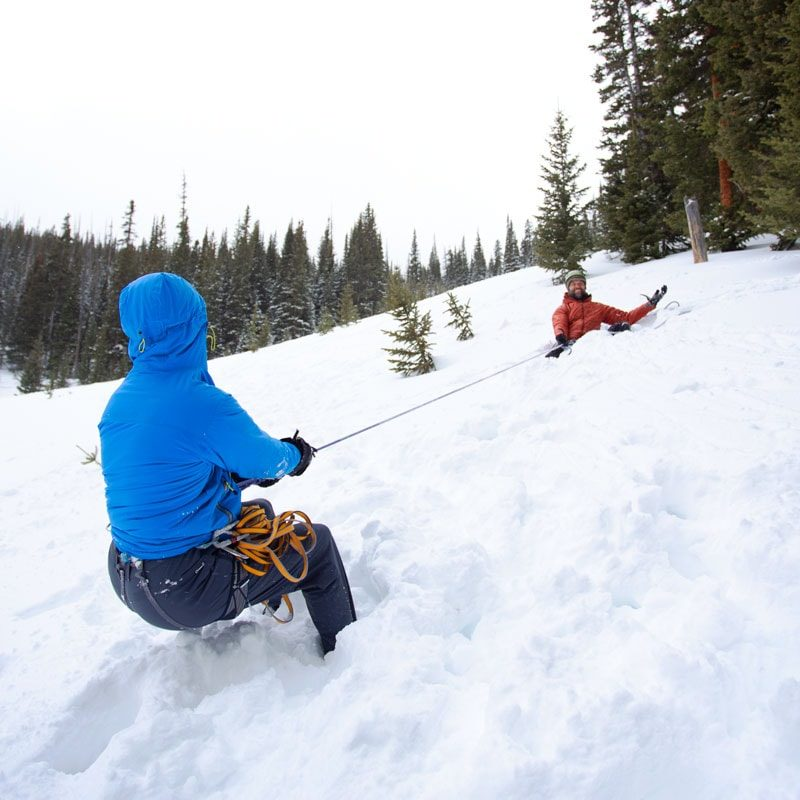 A student leans back on an anchor to test how much it can hold. The instructor, sitting in depression that he has dug into the snowy slope, casually holds the climbers weight.