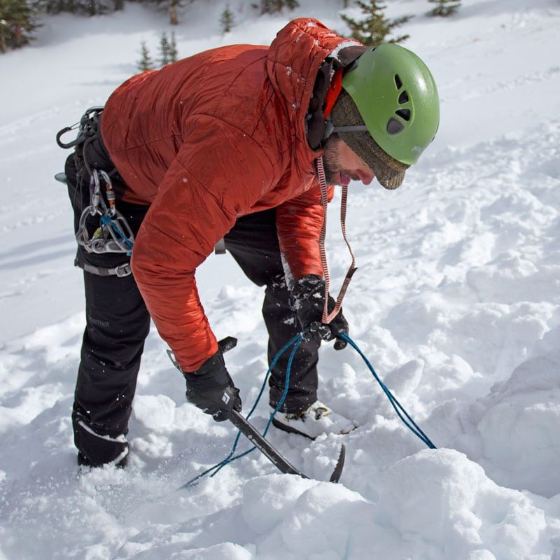 An instructor digs in the snow with his mountaineering axe on a Winter Anchor Building course in Colorado.