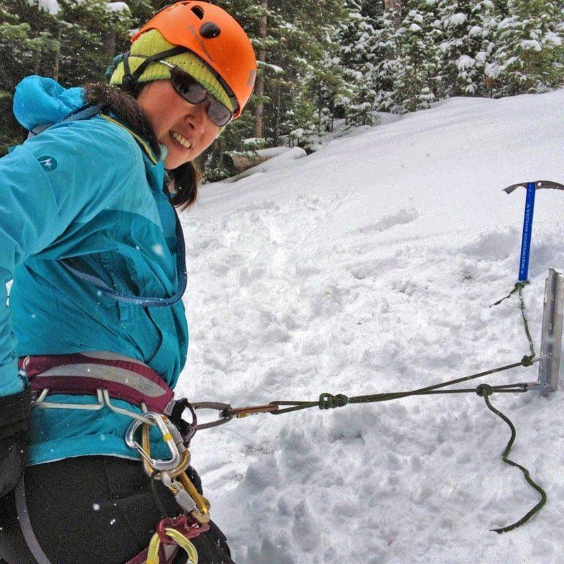 Colorado Mountain School Guide, Norie Kizaki, demonstrates a simple snow anchor built with a snow picket and a mountaineering axe.