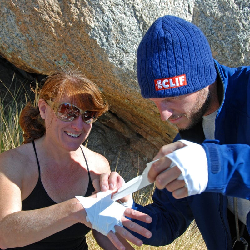 Colorado Mountain School Guide, Clint Locks, helps a student tape her hands on a Crack Climbing Course near Boulder, Colorado.