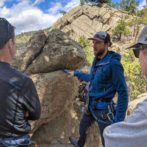 Colorado Mountain School Guide, Ben Markhart, teaches a group of climbers how to place a cam in crack in order to build a rock climbing anchor.