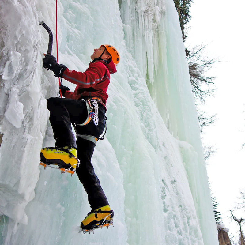 An ice climber eyes up his next move during a lesson in Colorado that teaches how to climb vertical ice flows.