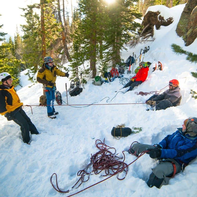 A group on students practice building and loading anchors during a mountaineering course in Colorado.