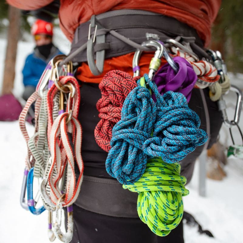 A mountaineer's harness, consisting of alpine quickdraws, cordlettes, prussiks and a belay device.