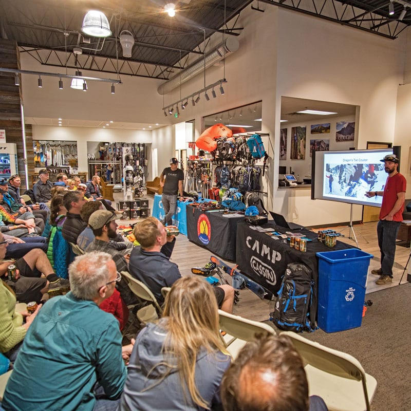 An AIARE avalanche instructor presents a slideshow to a crowd of people during an avalanche awareness clinic in Boulder, Colorado.