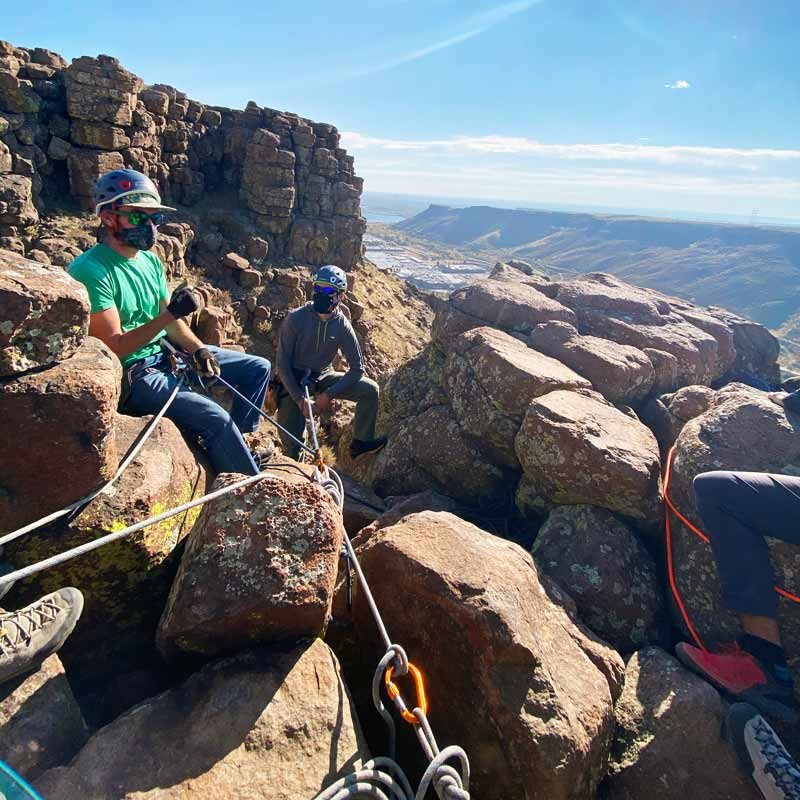 AMGA SPI Instructor, Rainbow Weinstock, teaches a group of aspiring climbing guides how to build a top-rope anchor at the top of a climb.