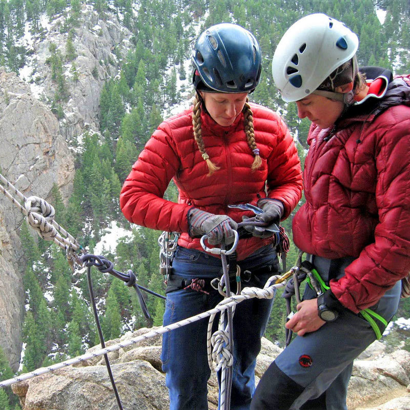 Two aspiring AMGA Single Pitch Instructors manage an anchor station at the edge of a cliff.