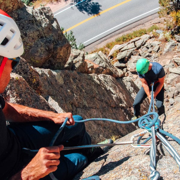 AMGA Instructor top-belays a climber down a single-pitch rappel on an AMGA SPI Exam.