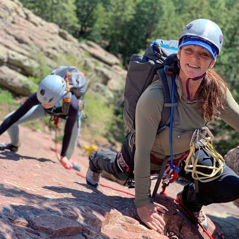A pair of rock climbers move up the Flatirons behind their climbing guide.
