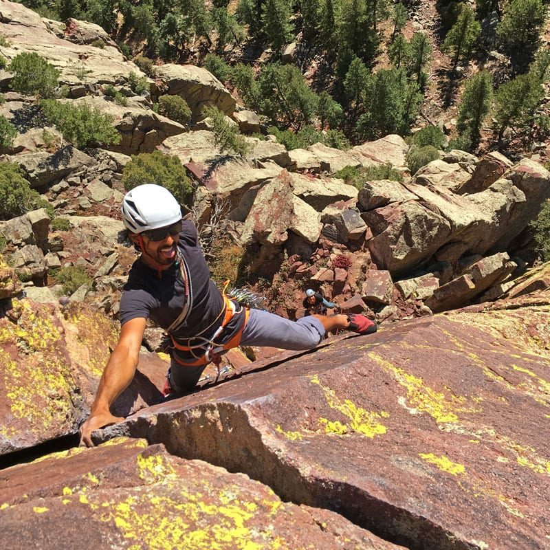 Colorado Mountain School Guide Japhy Dhungana leads the first pitch of a rock climb in Eldorado Canyon State Park.