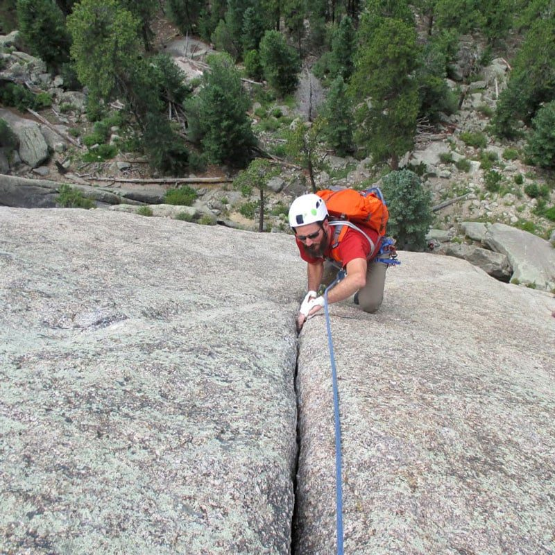 A climber jams his hands into a crack to ascend a climb on Lumpy Ridge in Rocky Mountain National Park, Colorado.