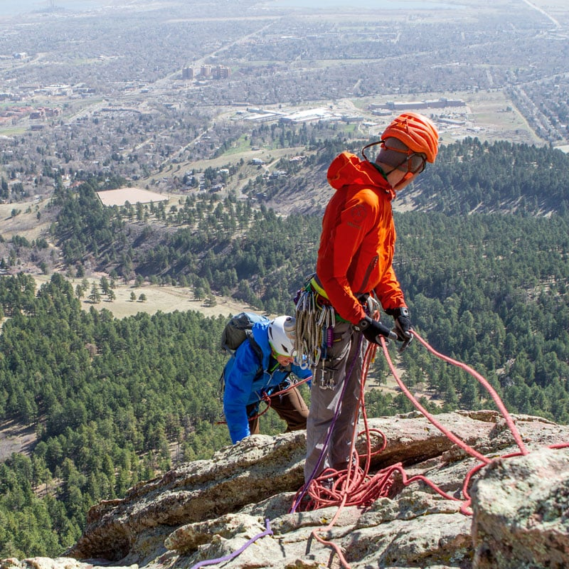 A climber nears the anchor as the guide belays from above on the First Flatiron - high above Boulder, Colorado.