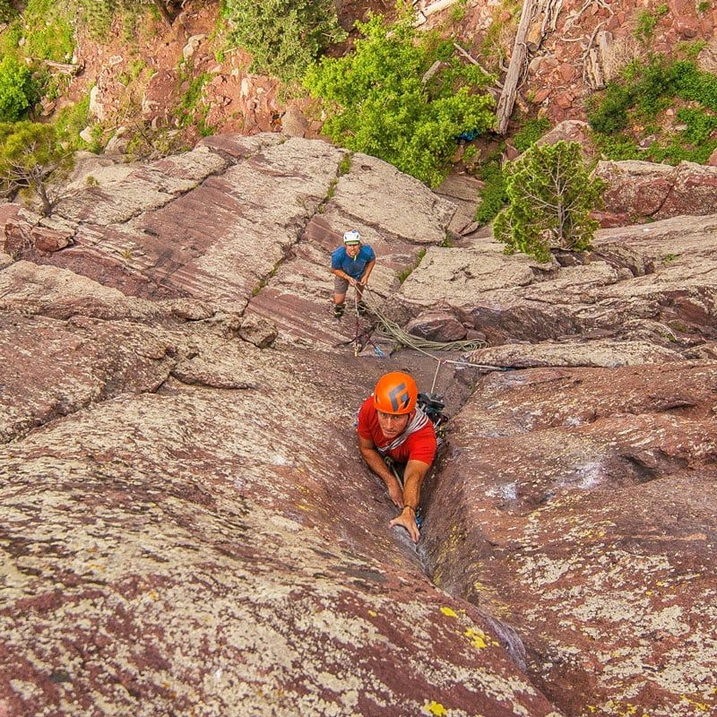 A rock climber reaches for a hold on an upper pitch of Long John Wall in Eldorado Canyon State Park.