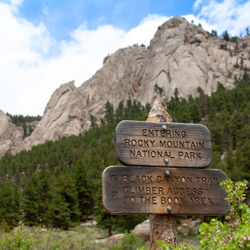 """A sign reads """"Entering Rocky Mountain National Park"""" with the climbing crags of Lumpy Ridge in the background."""