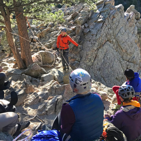 An AMGA Instructor teaches students how to safely access the top of a cliff on an SPI course near Denver, Colorado.