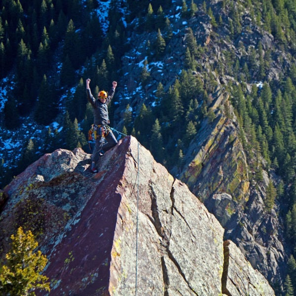 A rock climber raises his arms in the air on the summit of Redgarden Wall, Tower One in Eldorado Canyon State Park.