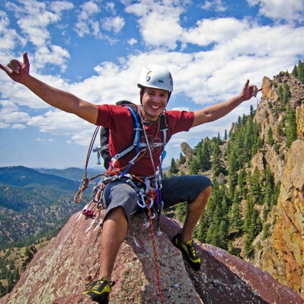 A rock climber celebrates atop Redgarden Wall, Tower One in Eldorado Canyon State Park.