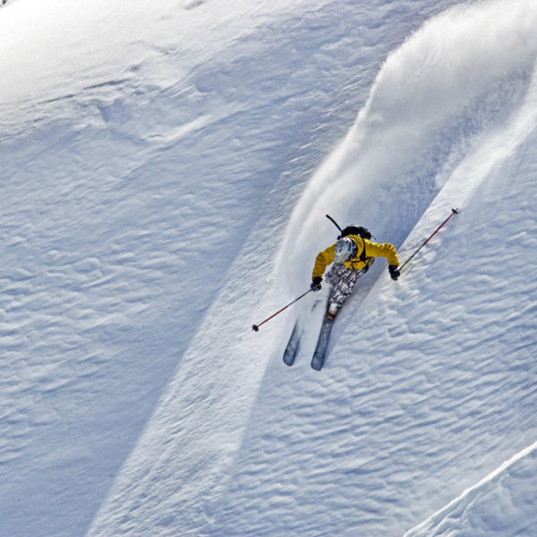 A backcountry skier carves powder on steep descent.