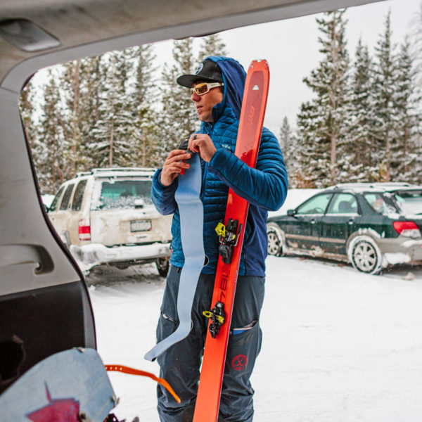 A student on a ski mountaineering course puts skins on his skis.