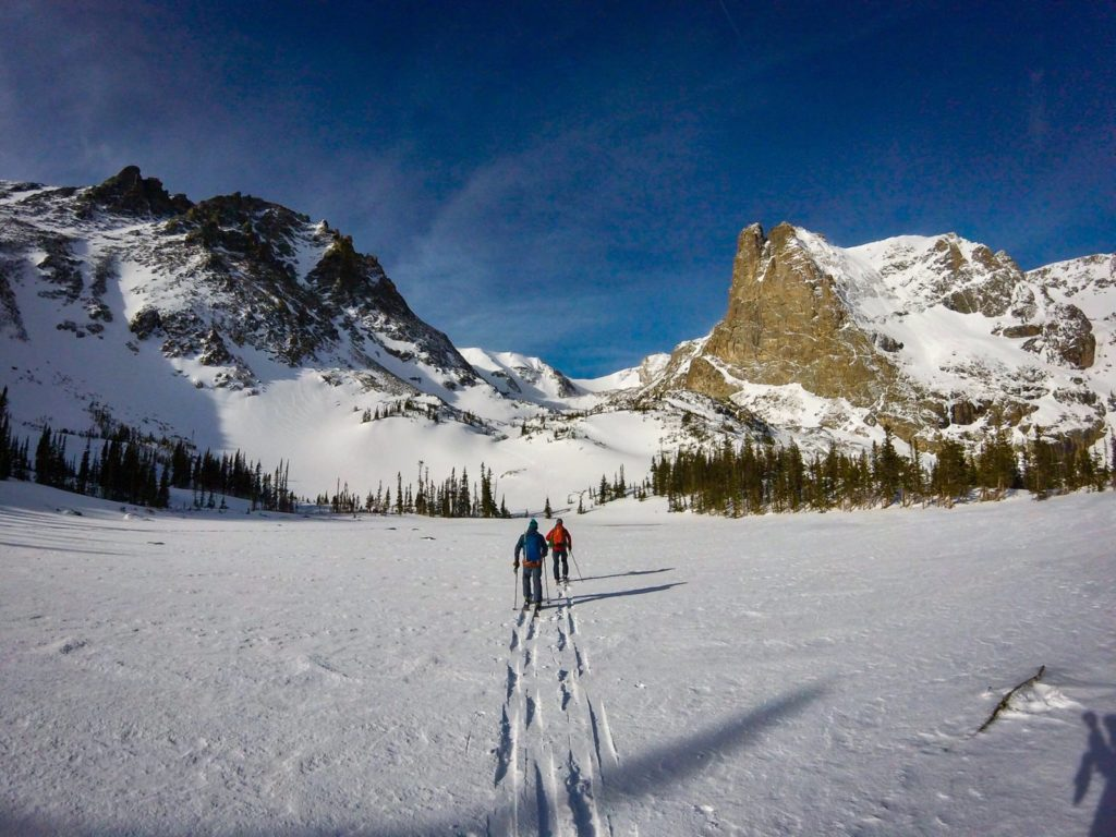 Two students on an Intro to Ski Mountaineering course ski tour into Rocky Mountain National Park before ascending and descending mountains.