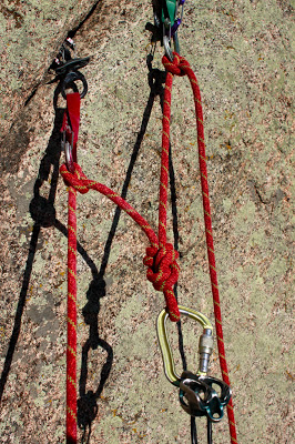 A simple rock climbing anchor is built by using the climbing rope. A single cam and two more equalized cams are brought to a masterpoint. It is here that the lead climber will belay up the follower.