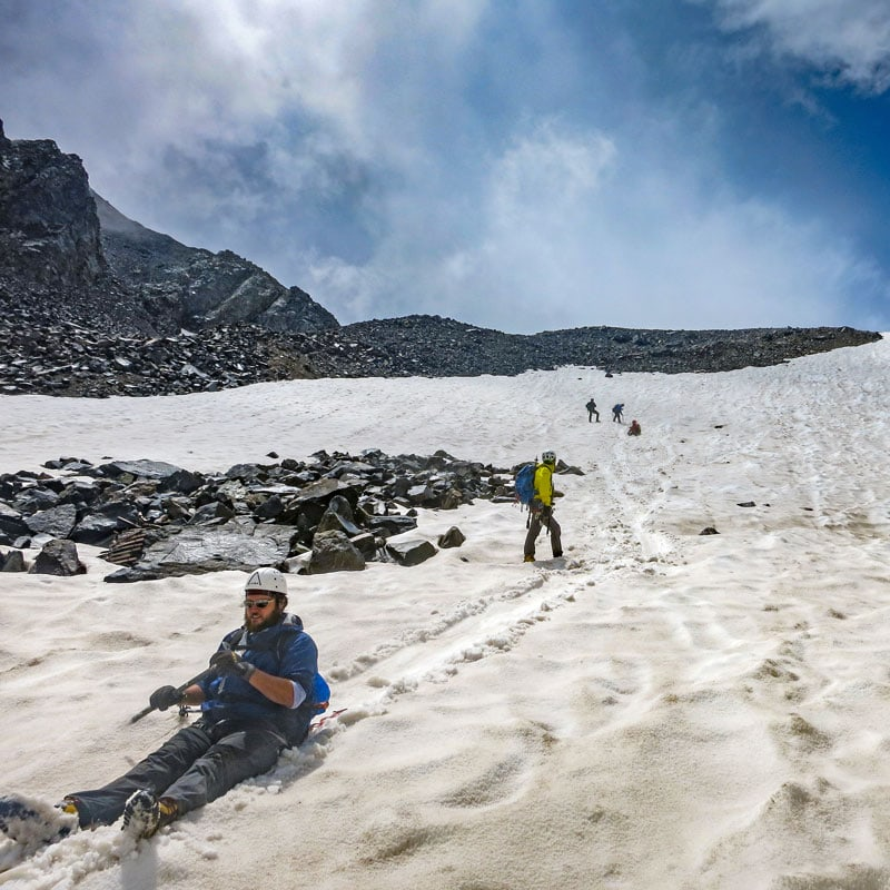 A mountaineer glissades down a snow slope on Castle Peak - a 14er in Colorado.