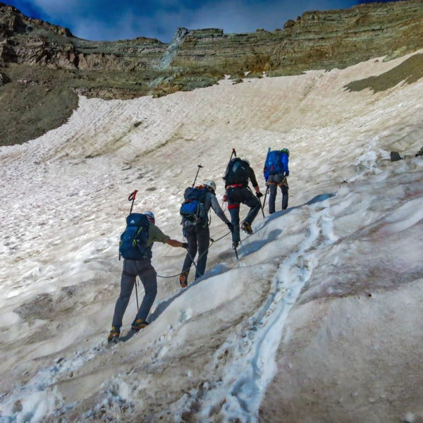 Four mountaineers climb a snow field on Castle Peak during a two-day course that takes place on the Fourteener in Colorado.