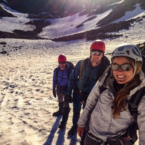 Three climbers boot up a snow field on Castle Peak.