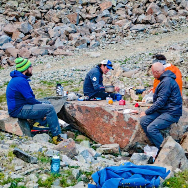 A group of mountaineers cook on a stove that is perched on a boulder at basecamp on Castle Peak.