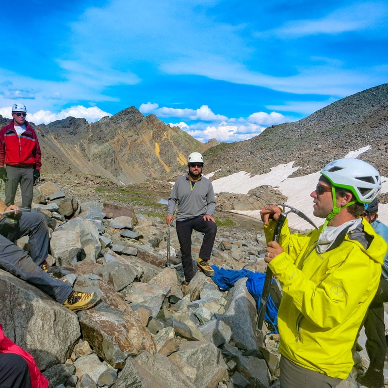 A guide teaches a group of mountaineers about climbing equipment. He's holding a mountain axe on location on Castle Peak - a Fourteener in Colorado.