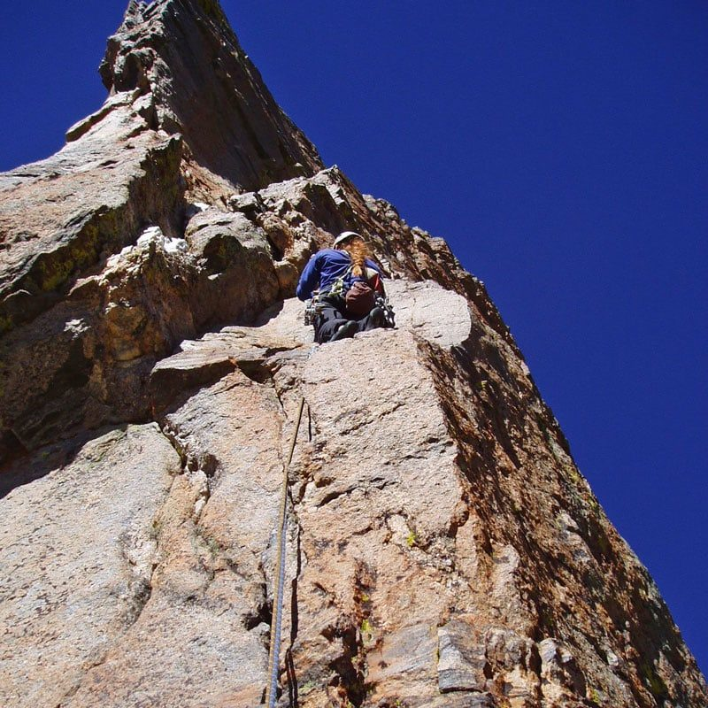 A climber rests momentarily on a ledge on the upper pitches of The South Face of the Petit Grepon.