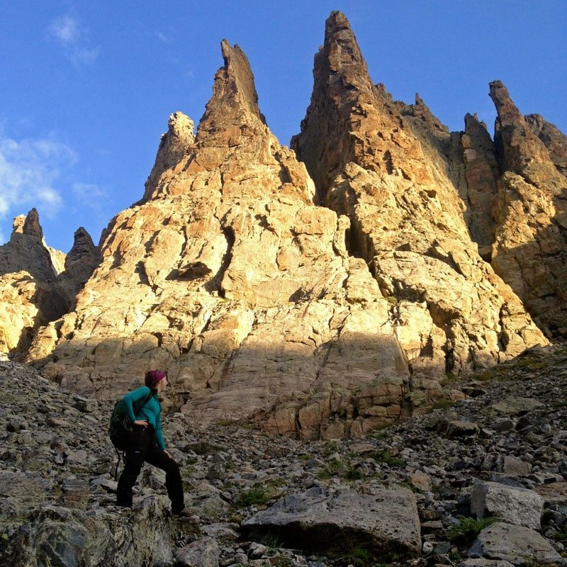 An alpine rock climber stands below the the rock apron at the base of the Petit Grepon in early morning light.