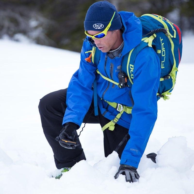 A backcountry skier searches through avalanche debris using an avalanche beacon on an AIARE Level 1 avalanche course near Denver, Colorado.