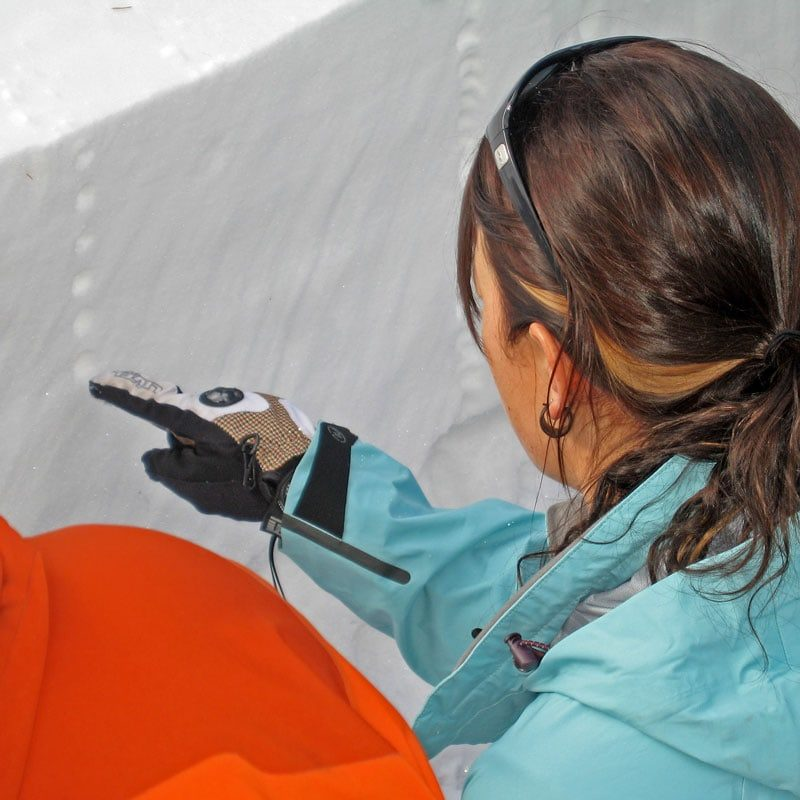 A student on an AIARE Level 1 avy course performs a test to find strong and weak layers in the snowpack by poking the sidewall of a snow pit.