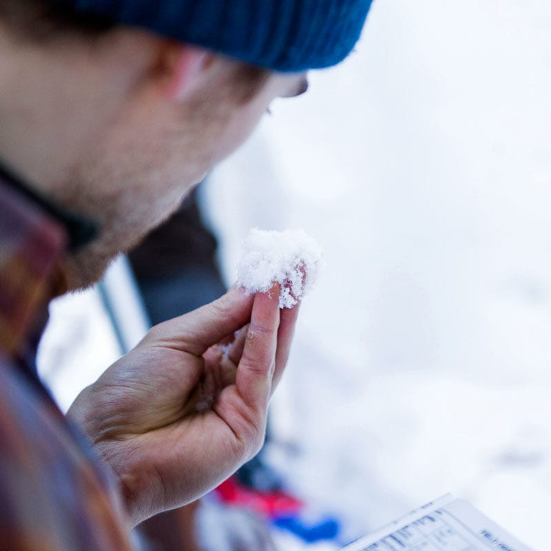 A student on an avalanche safety training course inspects a handful of snow crystals.