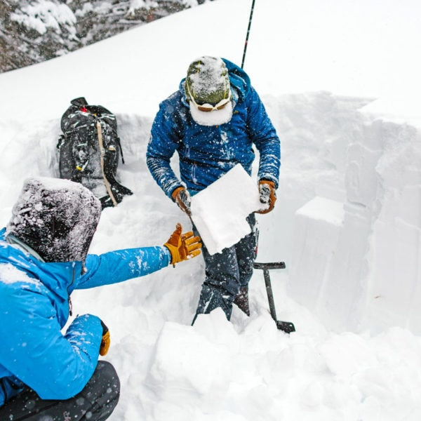 An avy 1 course instructor shows students what a wind slab looks like. He holds up a slab of snow that has fractured during extended column compression test.