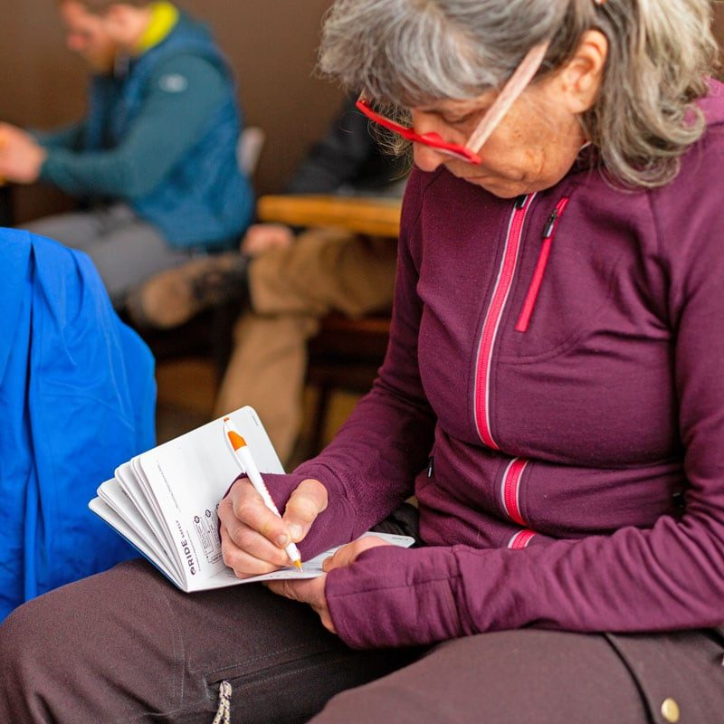 A student takes notes in an AIARE field book during a level 1 avalanche safety lesson in Denver, Colorado.