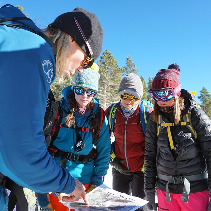 A group of students study a topographic map in preparation for a lesson in backcountry travel. The AIARE Level 1 course teaches backcountry skiers and splitboarders to safely navigate through avalanche terrain.