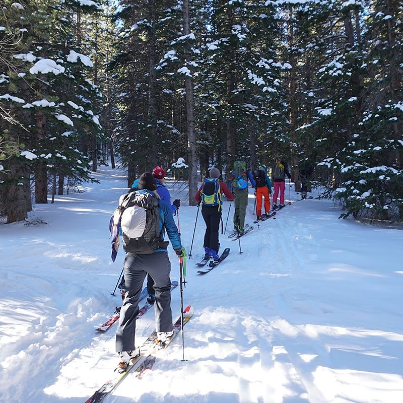 Backcountry skiers and splitboarders head up the trail on a Level 1 avy training course near Denver.