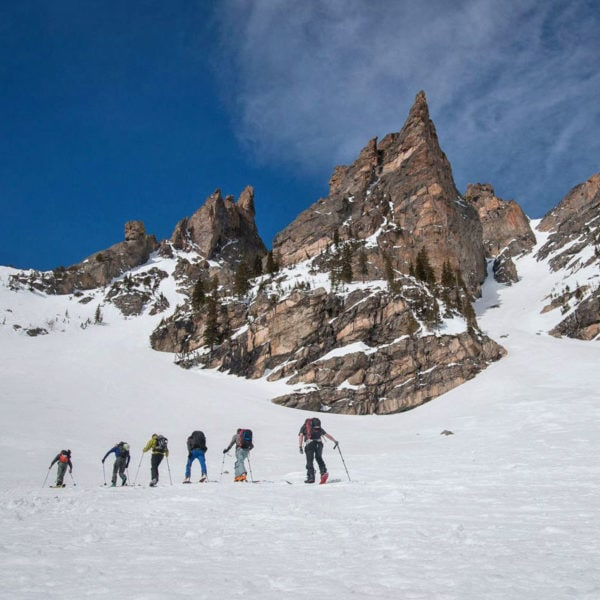 A group of backcountry skiers skin uphill on an avalanche safety training course in Colorado.