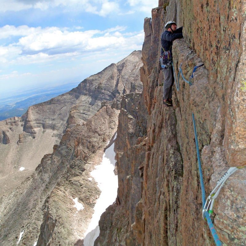 Colorado Mountain School Employee, Luke Terstriep, leads the final traversing pitch of the Casual Route on The Diamond, Longs Peak, Rocky Mountain National Park, Colorado.