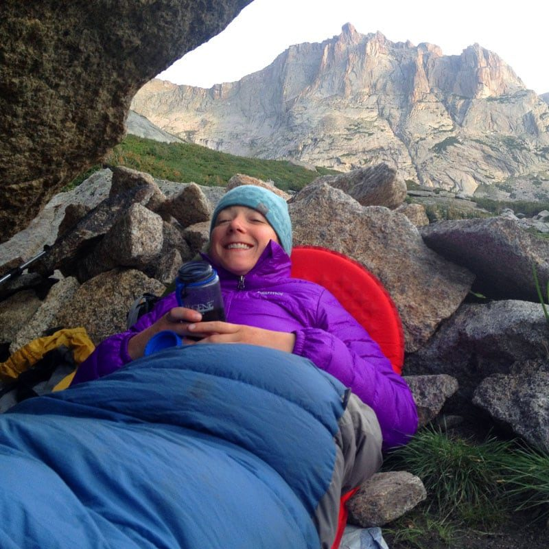 A rock climber lies comfortably in a bivouac cave below Spearhead in Rocky Mountain National Park.