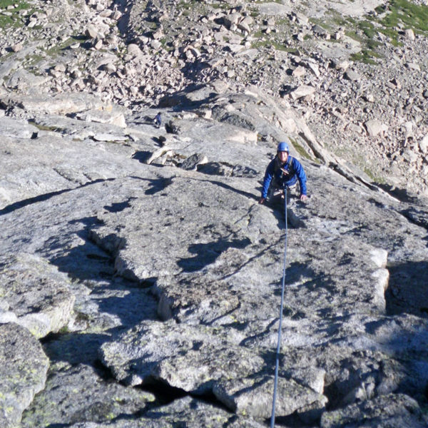 A climber looks up from mid-way up a rock climb on The Spearhead formation in Rocky Mountain National Park.