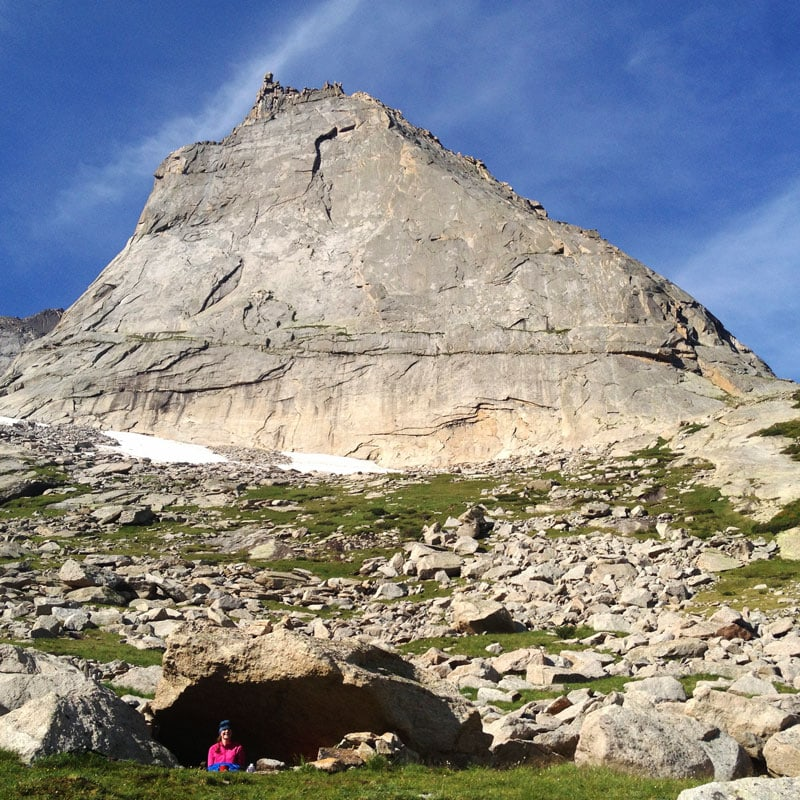 A rock climber sits in a bivy cave with Spearhead looming large behind her.
