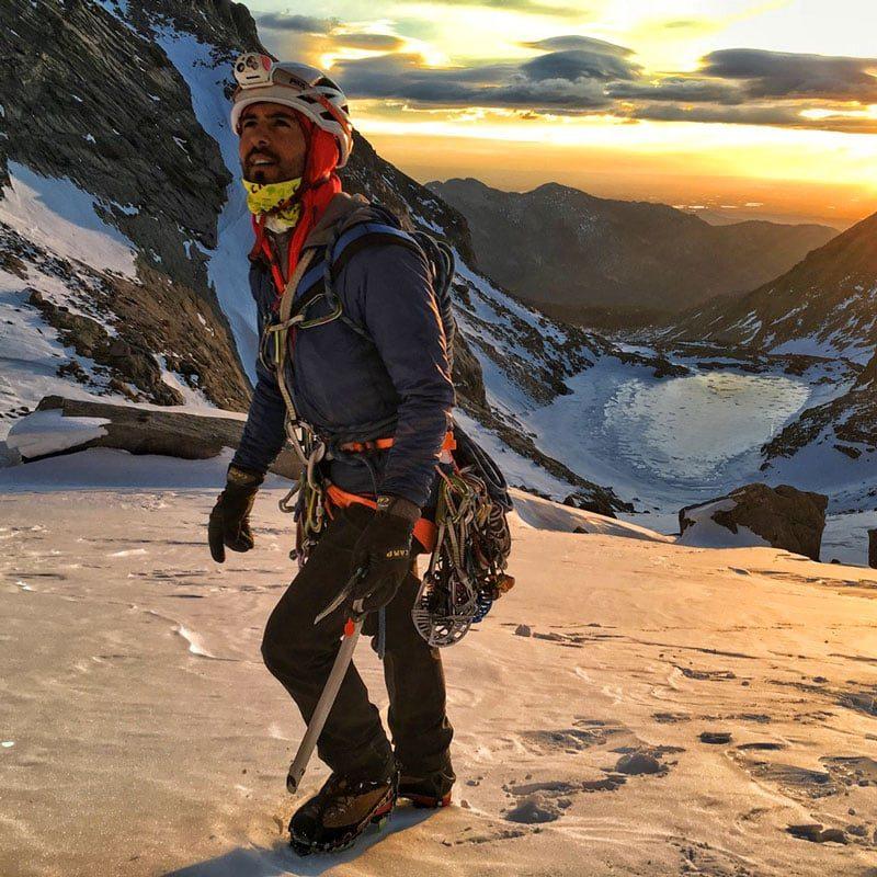 A climber approaches The Diamond on Longs Peak at sunrise via Mills Glacier.