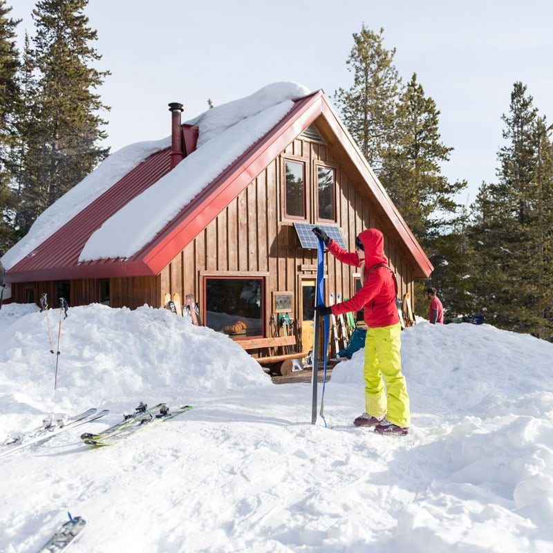 A student on an avalanche training hut trip places skins on his skis in preparation for the day's lesson.
