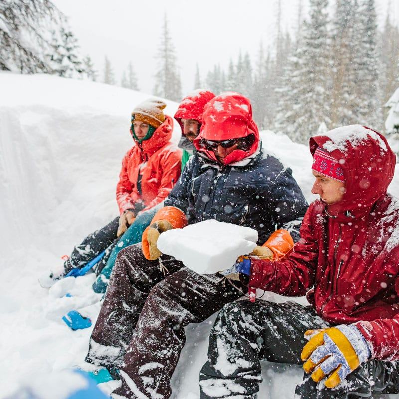 A group of backcountry skiers and splitboarders sit on the edge of a snow pit during a AIARE Level 1 Avalanche course near Denver, Colorado.