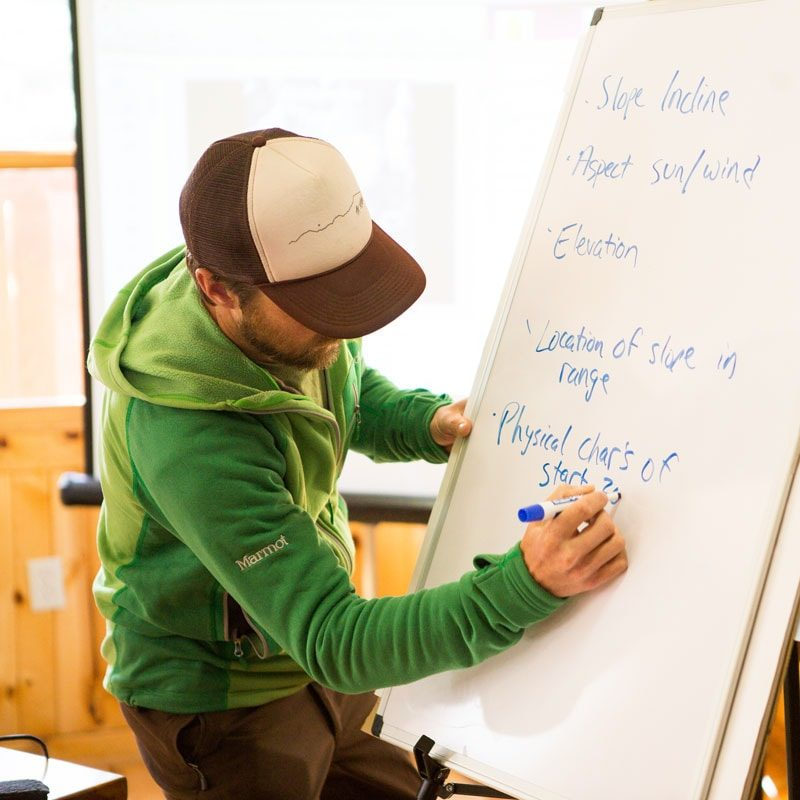 An AIARE 1 course instructor writes on white board during a lesson on snow slopes in an avalanche training course near Denver, Colorado.
