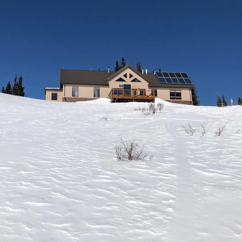 The Broome Hut sits on a snowy slope in the mountains of Colorado.