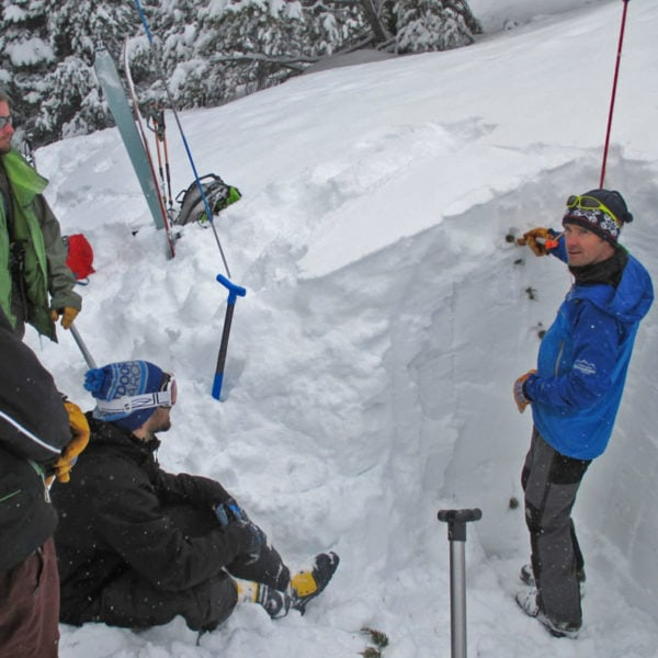 Avy instructor, Ian Fowler, stands in a snow pit while teaching students a lesson in snowpack stability on an AIARE 2 course in Colorado.
